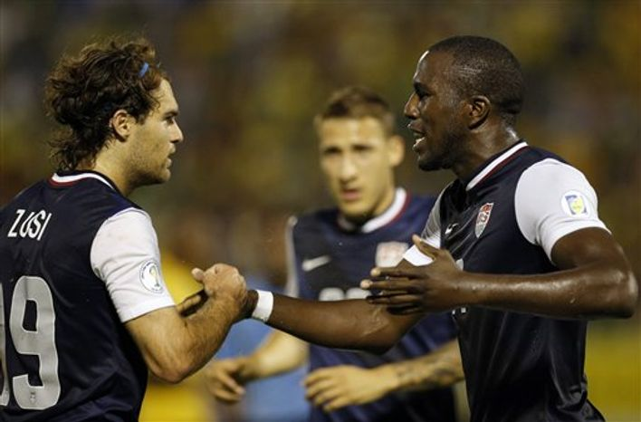 United States' Jozy Altidore, right, celebrates with teammate Graham Zusi after scoring during a 2014 World Cup qualifying soccer match against Jamaica in Kingston, Jamaica, Friday, June 7, 2013. (AP Photo/Andres Leighton)