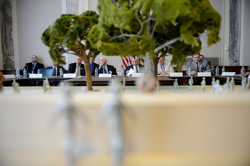 members of the Eisenhower Memorial Commission can be seen through a model of the proposed Eisenhower Memorial, displayed at a public meeting on Capitol Hill, Washington, D.C., Wednesday, June 19, 2013. The Commission met to discuss the continuing controversy over Frank Gehry's design for a memorial honoring Dwight D. Eisenhower. (Andrew Harnik/The Washington Times)