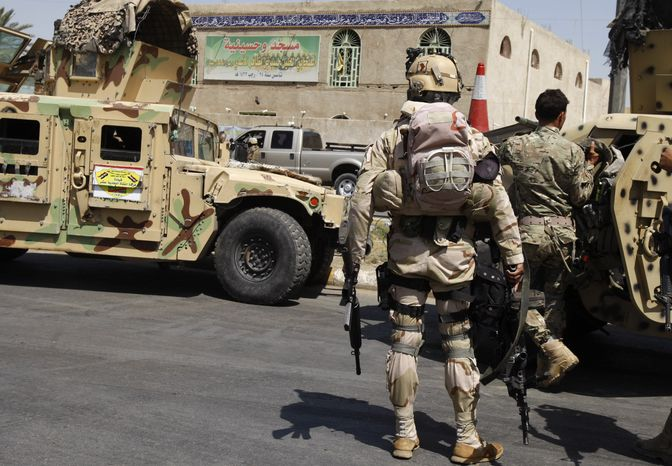 Security forces stand guard at the Habib ibn Mathaher mosque in Baghdad on Tuesday, June 18, 2013, after two suicide bombers blew themselves up at the Shiite mosque, Iraqi officials said. (AP Photo/Karim Kadim)