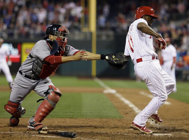 Jimmy Rollins is just out of reach of the tag of Nationals catcher Kurt Suzuki. The Nationals lost to the Phillies on Tuesday night and fell to 34-36 on the season. (Associated press photo)