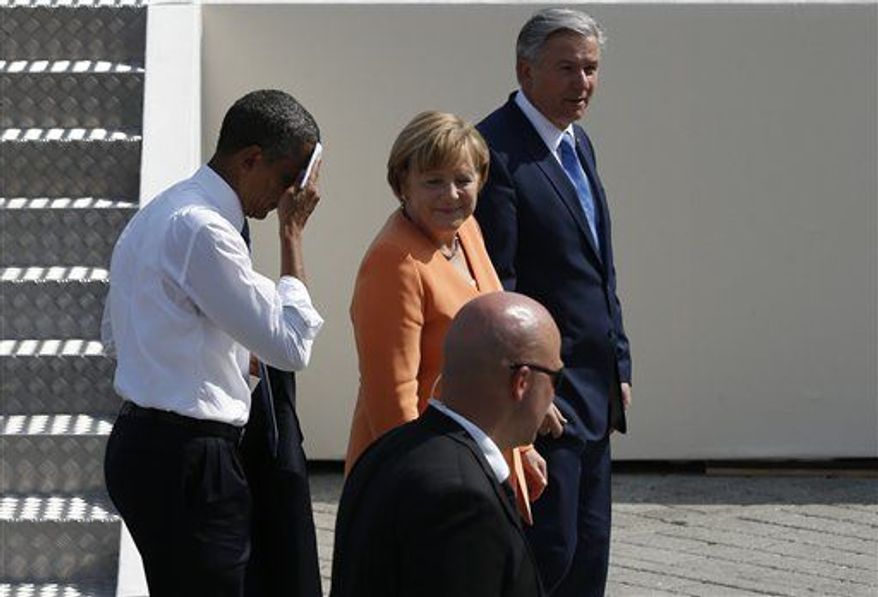 President Obama, left, wipes his face as he leaves the stage with German Chabcellor Angela Merkel, center, and Berlin's Mayor Klaus Wowereit after he delivered a speech in front of Brandenburg Gate in Berlin Wednesday, June 19, 2013. (Associated Press)