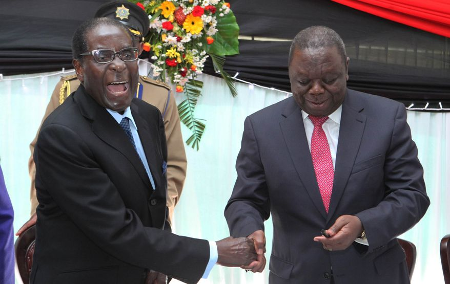 ** FILE ** In this Wednesday May 22, 2013, file photo Zimbabwean President Robert Mugabe, left, shakes hands with Prime Minister Morgan Tsvangirai after he signed the new constitution into law at State house in Harare. Zimbabwe's highest court on Friday, May 31, 2013, ordered Mugabe to hold elections by the end of July, chiding the longtime leader for what it said was a ''violation of his duties'' for not proclaiming the date earlier. (AP Photo/Tsvangirayi Mukwazhi, File)