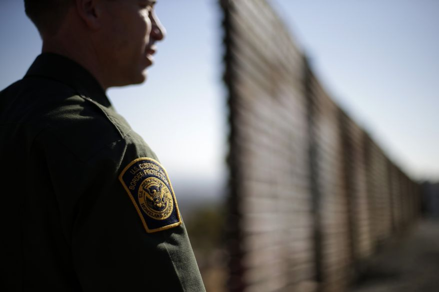 **FILE** U.S. Border Patrol agent Jerry Conlin looks to the north on June 13, 2013, near where the border wall ends as is separates Tijuana, Mexico and San Diego. (Associated Press)