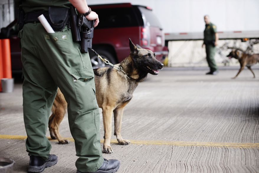 ** FILE ** U.S. Customs and Border Patrol agents and K-9 security dogs keep watch at a checkpoint station, on Feb. 22, 2013, in Falfurrias, Texas. Some drug smugglers caught at the highway checkpoint about an hour north of the Texas-Mexico border are losing their drugs, but not facing prosecution because cooperation between local and federal prosecutors has broken down. (Associated Press)