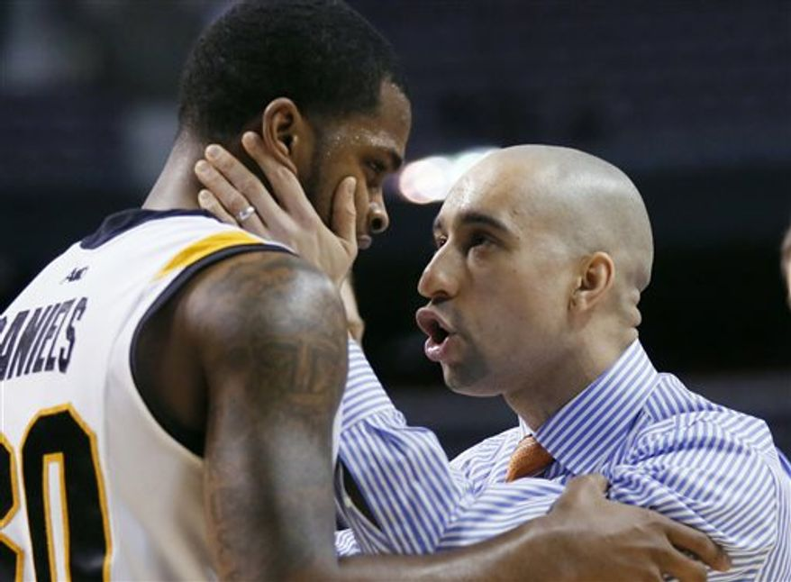 FILE - In this March 21, 2013 file photo, Virginia Commonwealth coach Shaka Smart, right, talks to guard Troy Daniels during the closing minutes of the team's 88-42 win over Akron in a second-round game of the NCAA men's college basketball tournament in Auburn Hills, Mich. Two years removed from leading VCU to the Final Four and becoming one of the biggest rock stars in college basketball, Smart has gone through his third consecutive offseason where he was mentioned for big job after big job. (AP Photo/Duane Burleson, File)
