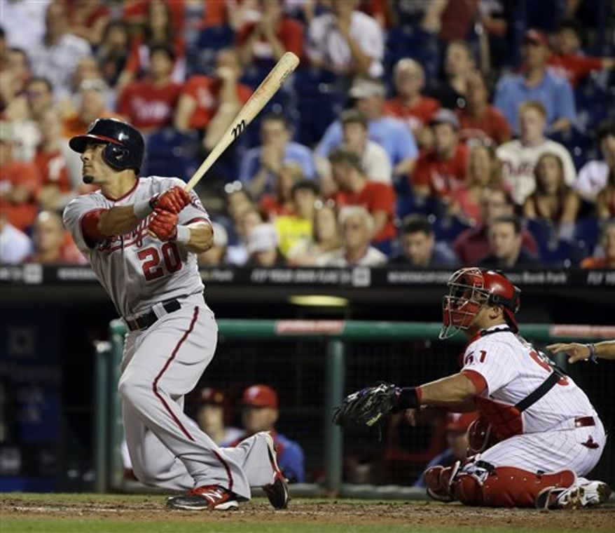 Washington Nationals' Ian Desmond, left, follows through after hitting a go-ahead grand slam off Philadelphia Phillies relief pitcher Michael Stutes in the 11th inning of a baseball game, Wednesday, June 19, 2013, in Philadelphia. Washington won 6-2 in 11 innings. At right is Carlos Ruiz. (AP Photo/Matt Slocum)