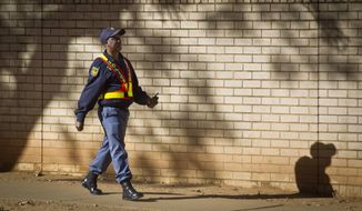 A South African policeman providing security walks past the outside of the Mediclinic Heart Hospital where former South African President Nelson Mandela is being treated in Pretoria, South Africa Saturday, June 15, 2013. (AP Photo/Ben Curtis)