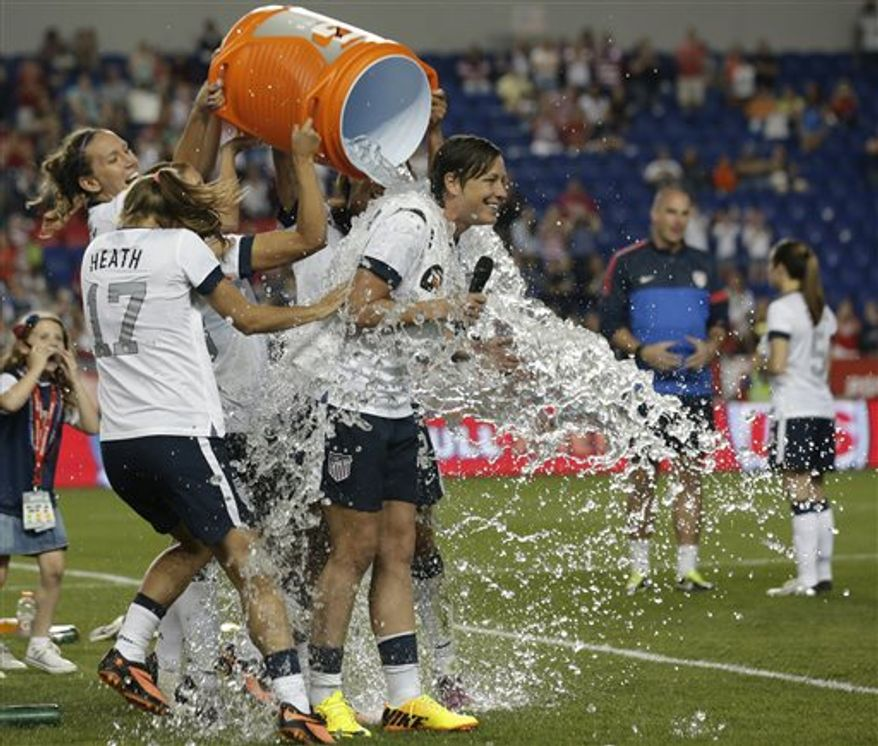 United States' Abby Wambach, right, is showered by teammates after an international friendly soccer match against South Korea at Red Bull Arena, Thursday, June 20, 2013, in Harrison, N.J. The U.S. won 5-0. Wambach is now the greatest goal scorer in international soccer. She scored four goals in the first half to break Mia Hamm's record. (AP Photo/Julio Cortez)