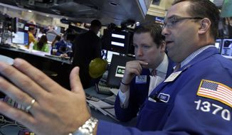 Trading specialists Gregg Maloney (left) and Anthony Matesic confer on the floor of the New York Stock Exchange on Thursday, June 20, 2013, in New York. Financial markets were sliding after the Federal Reserve said it could end its huge bond-buying program by the middle of next year. (AP Photo/Richard Drew)
