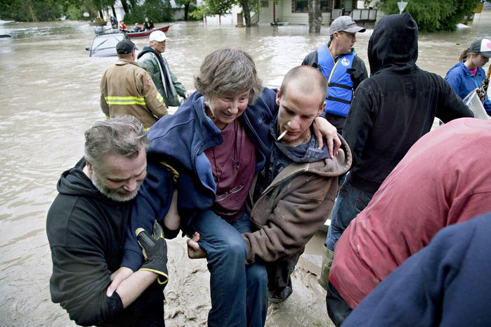 A woman is rescued from the flood waters in High River, Alberta on Thursday, June 20, 2013, after the Highwood River overflowed its banks. (AP Photo/The Canadian Press, Jordan Verlage)