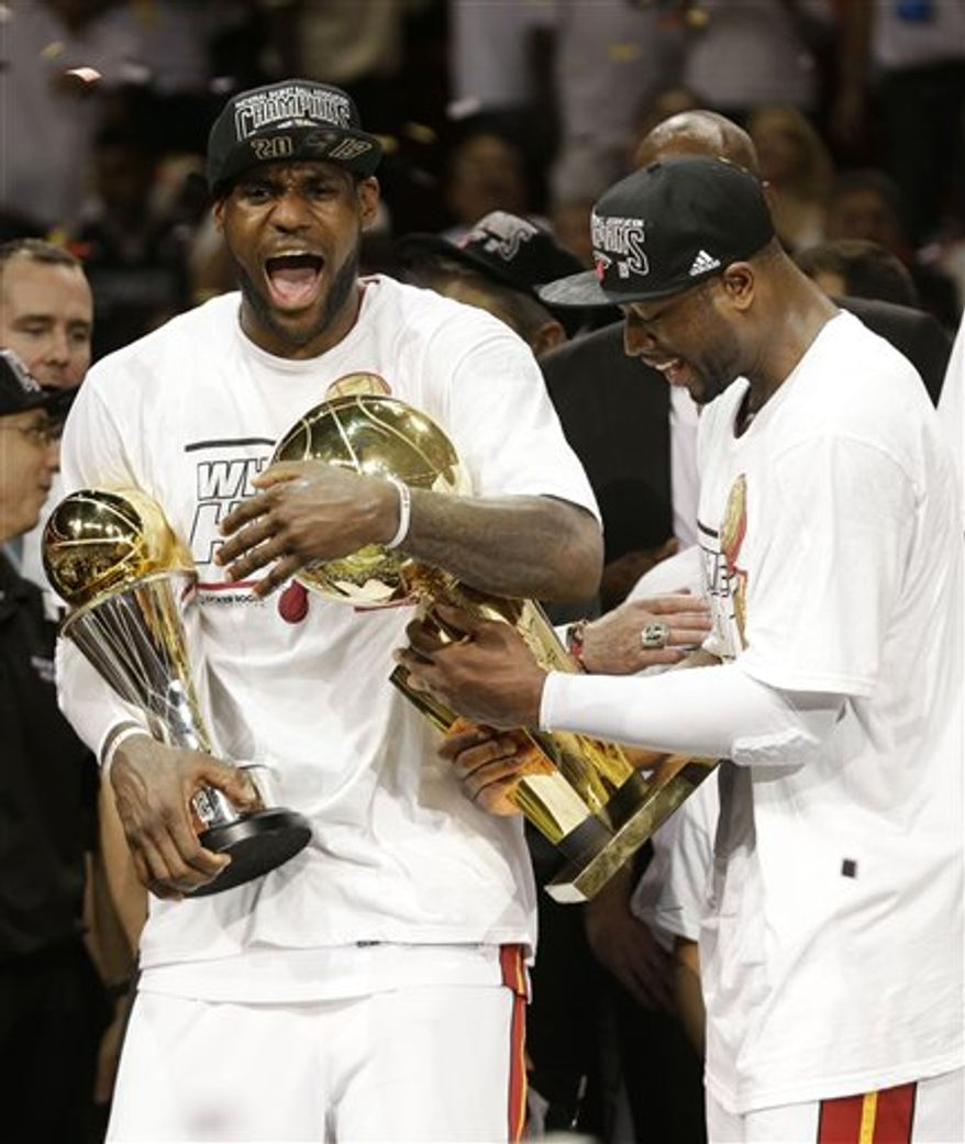 Miami Heat LeBron James, left and Dwyane Wade celebrate after defeating the San Antonio Spurs 95-88 to win their second straight NBA championship.(AP Photo/Lynne Sladky)