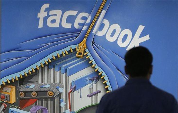 ** FILE ** A Facebook employee walks past a sign at Facebook headquarters in Menlo Park, Calif., March 15, 2013. Facebook on Friday, June 21, 2013 said a bug in its system caused 6 million users' contact information to be inadvertently exposed. (AP Photo/Jeff Chiu, File)