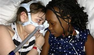 ** FILE ** Sarah Murnaghan, left, lies in her hospital bed next to adopted sister Ella on the 100th day of her stay in Children's Hospital of Philadelphia, May 30, 2013. (AP Photo/Murnaghan Family, File)