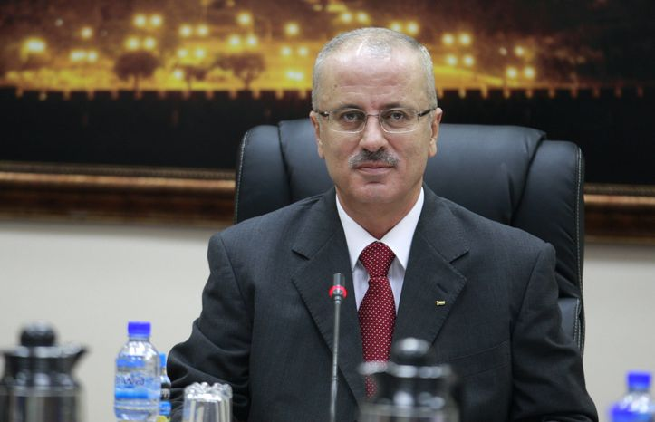 ** FILE ** Newly appointed Palestinian Prime Minister Rami Hamdallah attends his first meeting of the new Cabinet in the West Bank city of Ramallah on Tuesday, June 11, 2013. (AP Photo/Majdi Mohammed)