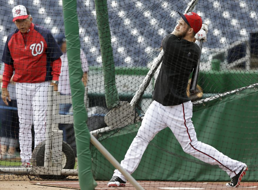 Bryce Harper took on-field batting practice on Sunday morning, under the watchful eye of Washington Nationals manager Davey Johnson. (Associated Press photo)