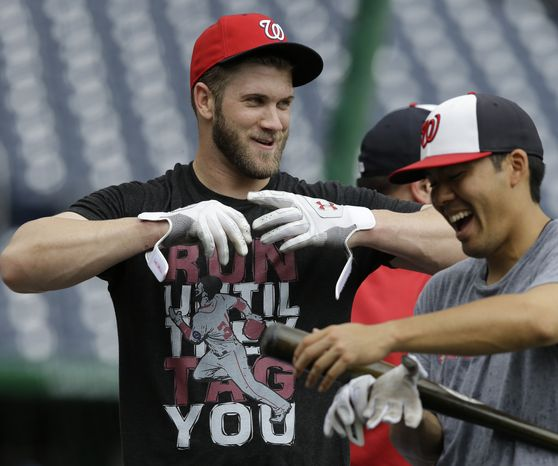 Bryce Harper and Kurt Suzuki laugh during early batting practice on Sunday at Nationals Park. (Associated press photo)