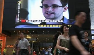 ** FILE ** A TV screen shows a news report of Edward Snowden, a former National Security Agency contractor who leaked top-secret documents about sweeping U.S. surveillance programs, at a shopping mall in Hong Kong Sunday, June 23, 2013. (AP Photo/Vincent Yu)