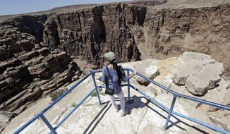 A tourist looks out from an observation point along the Little Colorado River Gorge on Saturday, June 22, 2013, on the Navajo reservation near Cameron, Ariz., outside the boundaries of Grand Canyon National Park, near where Nik Wallenda, the Florida-based daredevil, will bid to walk on a tightrope stretched across the gorge. (AP Photo/Rick Bowmer)