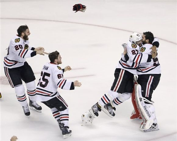 Chicago Blackhawks defenseman Johnny Oduya (27), of Sweden, hugs Chicago Blackhawks goalie Corey Crawford (50) after winning Game 6 of the NHL hockey Stanley Cup Finals 3-2 against the Boston Bruins, Monday, June 24, 2013, in Boston. (AP Photo/Charles Krupa)