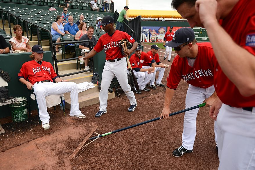 Pitcher Kyle Mertins (40), second from right, helps the ground crew sweep the dirt around the bullpen before the independent baseball league's Blue Crabs play the Camden RiverSharks at Regency Furniture Stadium, Waldorf, Md., Sunday, June 23, 2013. (Andrew Harnik/The Washington Times)