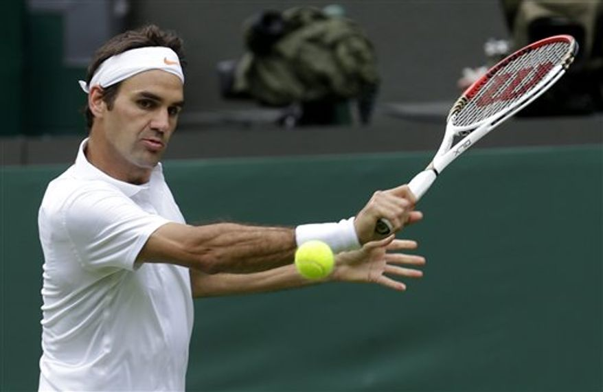 Roger Federer of Switzerland returns to Victor Hanescu of Romania during their Men's first round singles match at the All England Lawn Tennis Championships in Wimbledon, London, Monday, June 24, 2013. (AP Photo/Anja Niedringhaus)