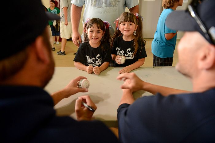 Twins Laura, center left, and Katie Coldin, 5, of Mechanicsville, Va., smile as they get their baseballs autographed by Blue Crabs pitchers Michael Ballard (48) left, and Charlie Manning (6), right at Regency Furniture Stadium, Waldorf, Md., Sunday, June 23, 2013. The Blue Crabs played the Camden RiverSharks, both teams part of the independent baseball leagues. (Andrew Harnik/The Washington Times)