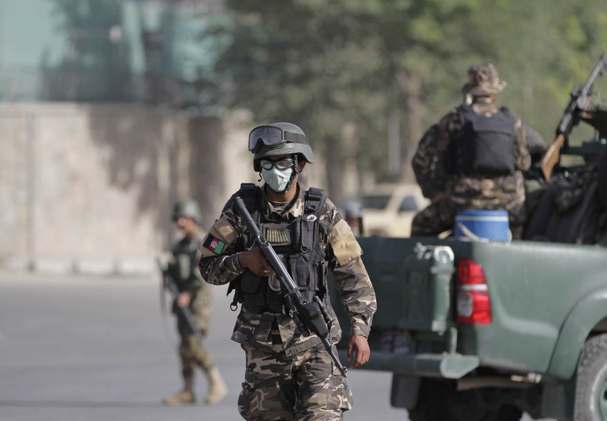 Afghan security and intelligence officers stand guard near the entrance gate of the presidential palace in Kabul, Afghanistan, Tuesday, June 25, 2013. Suicide attackers blew up a car bomb and battled security forces outside Afghanistan's presidential palace Tuesday after infiltrating one of the most secure areas of the capital. The army said the attackers were killed but knew of no other deaths. (AP Photo/Ahmad Jamshid)