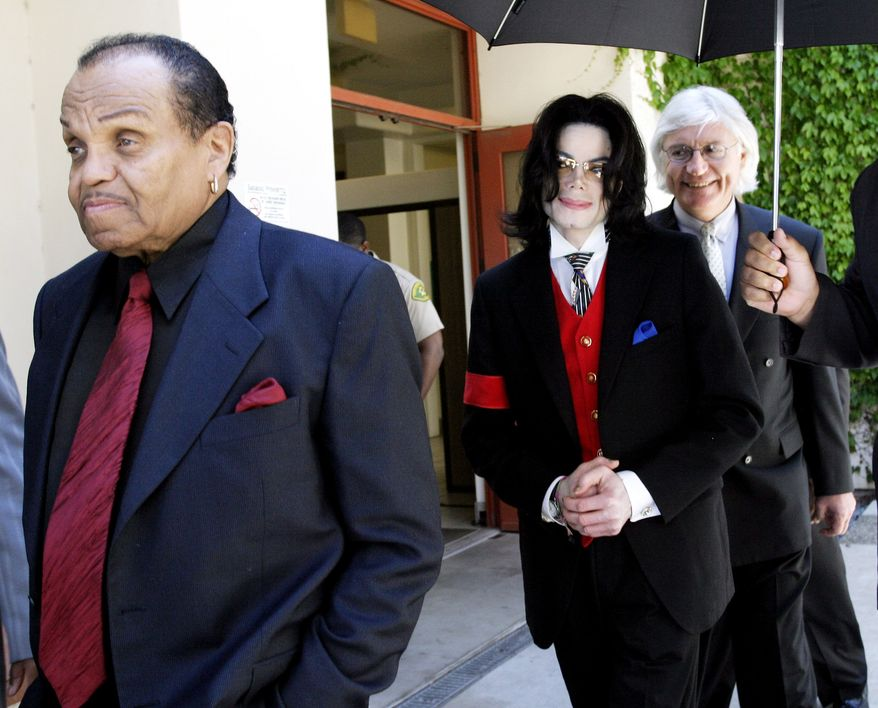 **FILE** Michael Jackson (center), his father Joe Jackson (left) and lawyer Thomas Mesereau leave the Santa Barbara County courthouse on April 29, 2005, in Santa Maria, Calif., as court is adjourned for the day in Michael Jackson's child molestation trial. Superior Court Judge Rodney S. Melville ruled Friday that prosecutors may use as evidence two books seized from the pop star's bedroom in 1993 that feature pictures of nude boys. (Associated Press/WireImage)