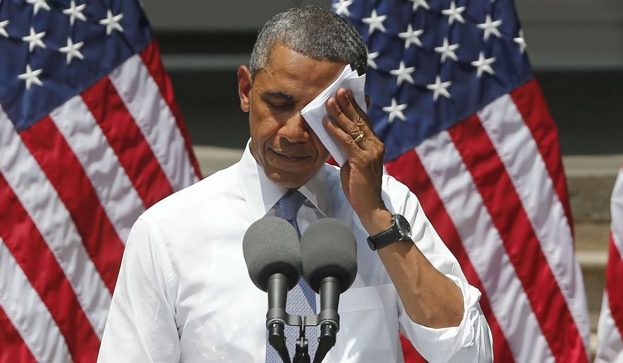 President Obama wipes his face as he speaks about climate change at Georgetown University in Washington on June 25, 2013. (Associated Press) **FILE**