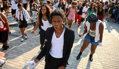"""Manny Love of Oxon Hill, Md., dresses as Michael Jackson, center, leads a group of dancers to Michael Jackson's """"Beat It"""" during a flash mob in front of the Howard Theatre to celebrate the life of the King of Pop on the 4th anniversary of his death, Washington, D.C., Tuesday, June 25, 2013. (Andrew Harnik/The Washington Times)"""
