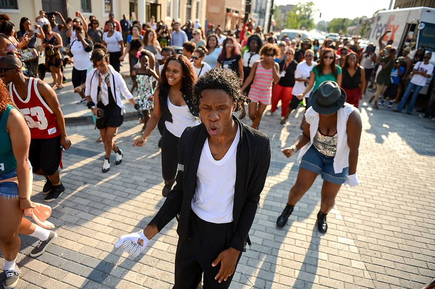 "Manny Love of Oxon Hill, Md., dresses as Michael Jackson, center, leads a group of dancers to Michael Jackson's ""Beat It"" during a flash mob in front of the Howard Theatre to celebrate the life of the King of Pop on the 4th anniversary of his death, Washington, D.C., Tuesday, June 25, 2013. (Andrew Harnik/The Washington Times)"