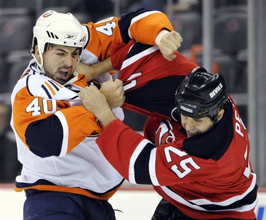 **FILE** New Jersey Devils' Andrew Peters (25) lands a right hand as he fights with New York Islanders' Joel Rechlicz (40) during the first period of a preseason NHL hockey game Tuesday, Sept. 29, 2009, in Newark, N.J. (AP Photo/Bill Kostroun)