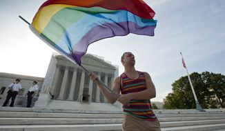 ** FILE ** Gay rights advocate Vin Testa waves a rainbow flag at dawn in front of the U.S. Supreme Court in Washington on Wednesday, June 26, 2013. In two separate and significant victories for gay rights, the high court struck down a provision of the Defense of Marriage Act denying federal benefits to married gay couples and cleared the way for the resumption of same-sex marriage in California. (Associated Press)