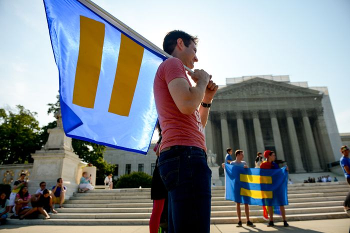 **FILE** Grant Olan (center), of Washington, D.C., joins crowds gathering in front of the Supreme Court building on June 26, 2013, for the California Proposition 8 case as a decision is expected to be announced on the last day of the court's term. (Andrew Harnik/The Washington Times)
