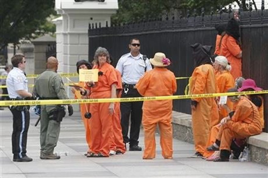 ** FILE ** U.S. Park Police arrest demonstrators wearing orange jumpsuits protesting the Guantanamo Bay military detention facility, Wednesday, June 26, 2013, at the north gate of the White House in Washington. President Obama was not at the White House at the time. (Associated Press)