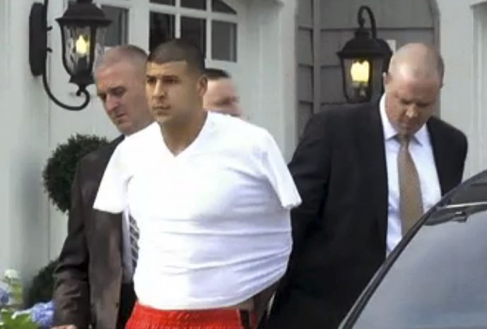 In this image taken from video, police escort Aaron Hernandez from his home in handcuffs in Attleboro, Mass., Wednesday, June 26, 2013. Hernandez was taken from his home more than a week after a Boston semi-pro football player was found dead in an industrial park a mile from Hernandez's house. (AP Photo/ESPN)
