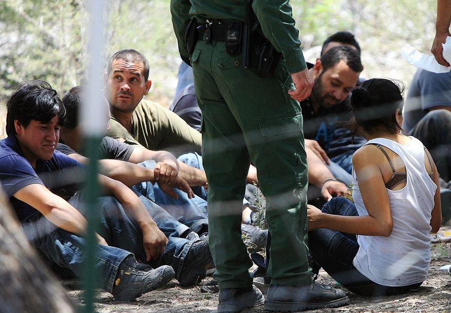 **FILE** People wait under a tree after they were detained by Border Patrol agents on June 25, 2013, at a field in Edinburg, Texas. Agents took into custody 69 people suspected of entering the country illegally. (Associated Press/The Monitor)