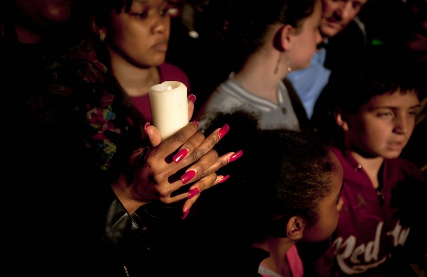A woman from a community group based in Pretoria holds a candle and sings religious songs to show appreciation and support for former South African President, Nelson Mandela, on the street outside the Mediclinic Heart Hospital where he is being treated in Pretoria, South Africa, Tuesday, June 25, 2013. (AP Photo/Ben Curtis)