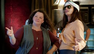 """Melissa McCarthy (left) and Sandra Bullock play a mismatched pair of law enforcement officers thrown together on a case in """"The Heat."""" (20th Century Fox via Associated Press)"""