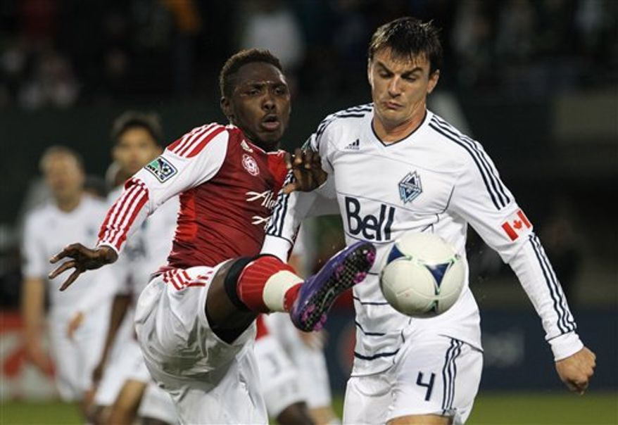 **FILE** Portland Timbers' Kalif Alhassan kicks the ball as Vancouver Whitecaps Alain Rochat (4) defends in the second half during an MLS soccer game Saturday, May 26, 2012, in Portland, Ore. The Whitecaps and the Timbers tied 1-1. (AP Photo/Rick Bowmer)