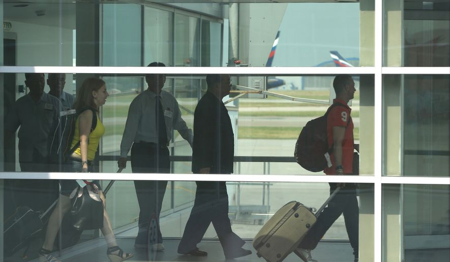 Passengers walk to board Aeroflot flight SU150 from Moscow to Havana, at Sheremetyevo airport in Moscow on June 27, 2013. (Associated Press)