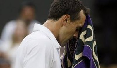 Bobby Reynolds of the United States wipes himself with a towel as he faces Novak Djokovic of Serbia in their Men's second round singles match at the All England Lawn Tennis Championships in Wimbledon, London, Thursday, June 27, 2013. (AP Photo/Kirsty Wigglesworth)