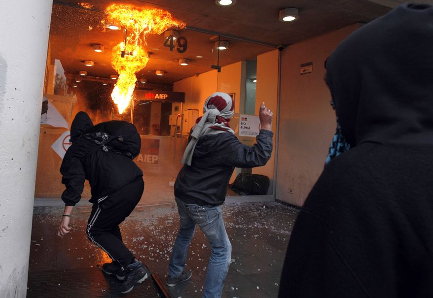 Demonstrators throw Molotov cocktails and rocks at an institute of technology during a nationwide demonstration in Santiago, Chile, Wednesday, June 26, 2013. (AP Photo/Luis Hidalgo, File)