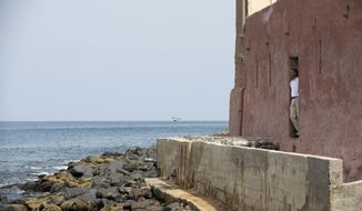 """President Barack Obama looks out of the """"door of no return"""" during a tour of Goree Island, Thursday, June 27, 2013, in Goree Island, Senegal. Goree Island is the site of the former slave house and embarkation point built by the Dutch in 1776, from which slaves were brought to the Americas. The """"door of no return"""" was the entrance to the slave ships. (AP Photo/Evan Vucci)"""