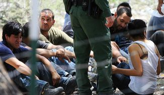People wait under a tree after they were detained by Border Patrol agents Tuesday, June 25, 2013, at a field in Edinburg, Texas. Agents took into custody 69 people suspected of entering the country illegally. (AP Photo/The Monitor, Gabe Hernandez)