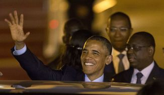 U.S. President Barack Obama waves as he boards a car after arriving at the airport in Dakar, Senegal, Wednesday, June 26, 2013. (AP Photo/Rebecca Blackwell)