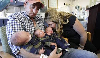 **FILE** Brittany Deen kisses her son, Elliot, who, along with his brothers Sidney (left) and Jenson, are held by the their father, Jason Deen at Sutter Memorial Hospital in Sacramento, Calif., on Nov. 14, 2012. The trio, born Nov. 8, are believed to be the heaviest triplets in the world with a combined weight of 20 pounds at birth. (Associated Press)