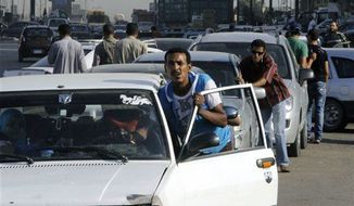 ** FILE ** Egyptian drivers push their cars as they wait in long queues at a gasoline station in Cairo, Egypt, June 25. As the streets once again fill with protesters eager to oust the president and Islamists determined to keep him in power, Egyptians are preparing for the worst: days or weeks of urban chaos. (Associated Press)