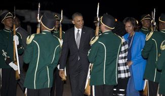 President Obama and first lady Michelle Obama arrive at Waterkloof Air Base, Friday, June 28, 2013, in Centurion, South Africa. The president is in South Africa, embarking on the second leg of his three-country African journey. (AP Photo/Evan Vucci)