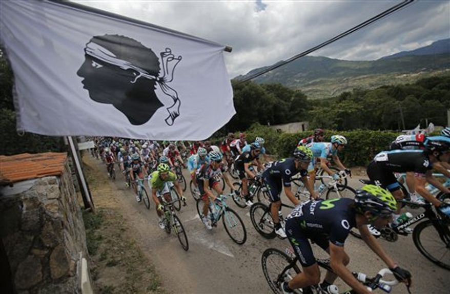 The pack passes a flag featuring a Moor's head, the Corsican emblem, during the first stage of the 100th edition of the Tour de France cycling race over 213 kilometers (133 miles) with start in Porto Vecchio and finish in Bastia, Corsica island, France, Saturday June 29, 2013. (AP Photo/Christophe Ena)